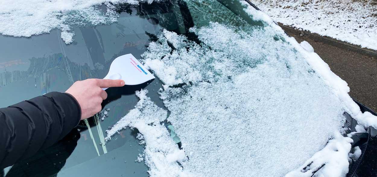 Eiskratzen im Winter auf der Winschutzscheibe